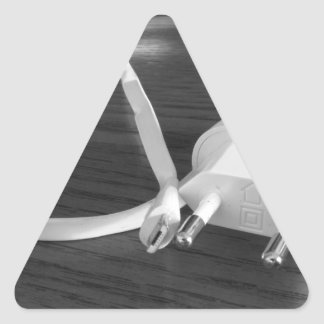 Weißes smartphone Ladegerät auf hölzerner Tabelle Dreieckiger Aufkleber