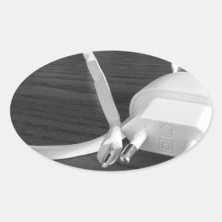 Weißes smartphone Ladegerät auf hölzerner Tabelle Ovaler Aufkleber