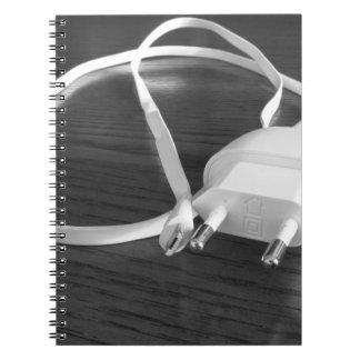 Weißes smartphone Ladegerät auf hölzerner Tabelle Spiral Notizblock
