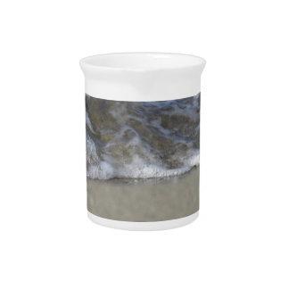 Welle des Meeres auf dem Sandstrand Getränke Pitcher
