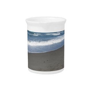 Wellen des Meeres auf dem Sand setzen auf den Krug