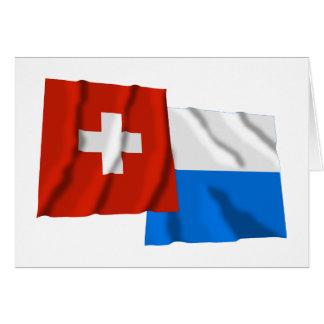 Wellenartig bewegende Flaggen der Schweiz u. der Karte