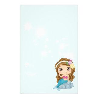 Wenig brünette Cartoon-Meerjungfrau, die auf Briefpapier