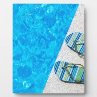 Zwei badenpantoffel auf Rand des Swimmingpools Fotoplatte