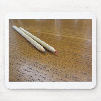 Zwei benutzte farbige Bleistifte auf hölzerner Mousepad