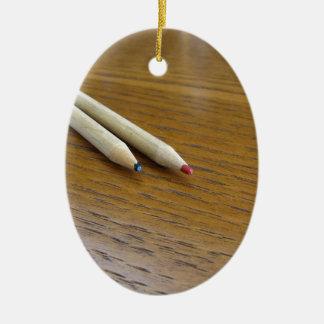 Zwei benutzte farbige Bleistifte auf hölzerner Ovales Keramik Ornament