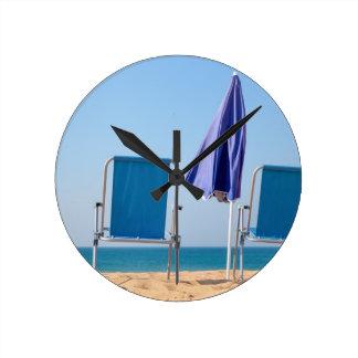 Zwei blaue Strandstühle und -sonnenschirm an Runde Wanduhr