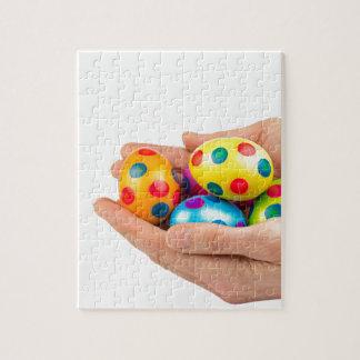 Zwei Hände, die gemalte Ostereier auf Weiß halten Puzzle