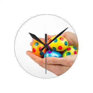 Zwei Hände, die gemalte Ostereier auf Weiß halten Runde Wanduhr