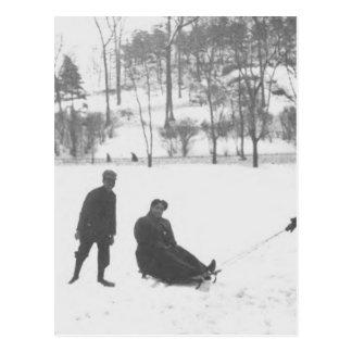Zwei Jungen, die zwei Mädchen auf Schlitten ziehen Postkarte