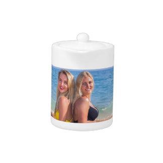 Zwei Mädchen sitzen auf Strand nahe blauem sea.JPG
