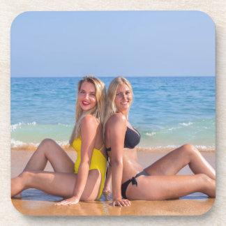 Zwei Mädchen sitzen auf Strand nahe blauem sea.JPG Getränkeuntersetzer