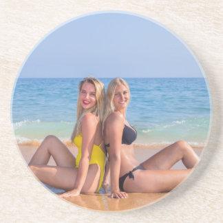 Zwei Mädchen sitzen auf Strand nahe blauem sea.JPG Sandstein Untersetzer