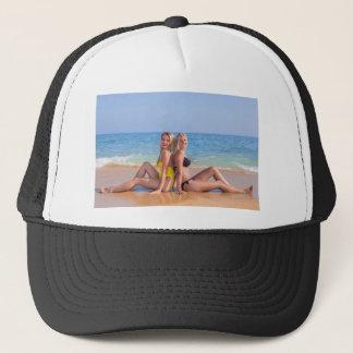 Zwei Mädchen sitzen auf Strand nahe blauem sea.JPG Truckerkappe