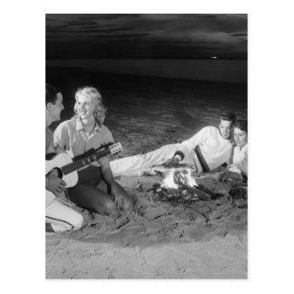 Zwei Paare auf dem Strand, der um Lagerfeuer sitzt Postkarte