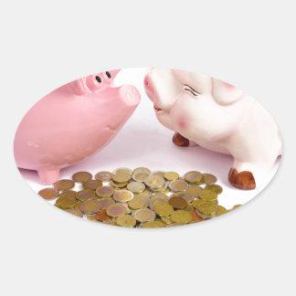 Zwei piggy Banken mit Euromünzen auf Weiß Ovaler Aufkleber