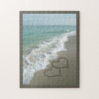 Zwei Sand-Herzen auf dem Strand, romantischer Puzzle