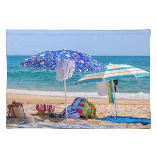 Zwei Sonnenschirme und Strandversorgungen an Tischset