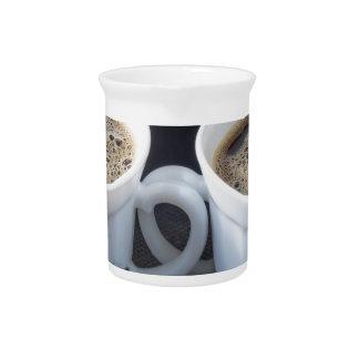 Zwei weiße Schalen mit schwarzem Kaffee und Schaum Krug