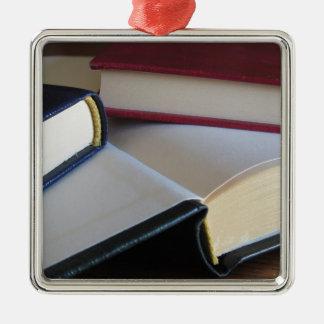 Zweite Hand bucht mit Leerseiten auf einer Tabelle Quadratisches Silberfarbenes Ornament